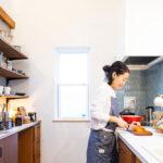 造作棚のあるキッチンに立つ女性