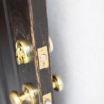 黒のドアに映えるゴールドの金物
