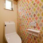 壁のアクセントクロスがかわいいトイレ
