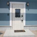 青い外壁に白い玄関ドア